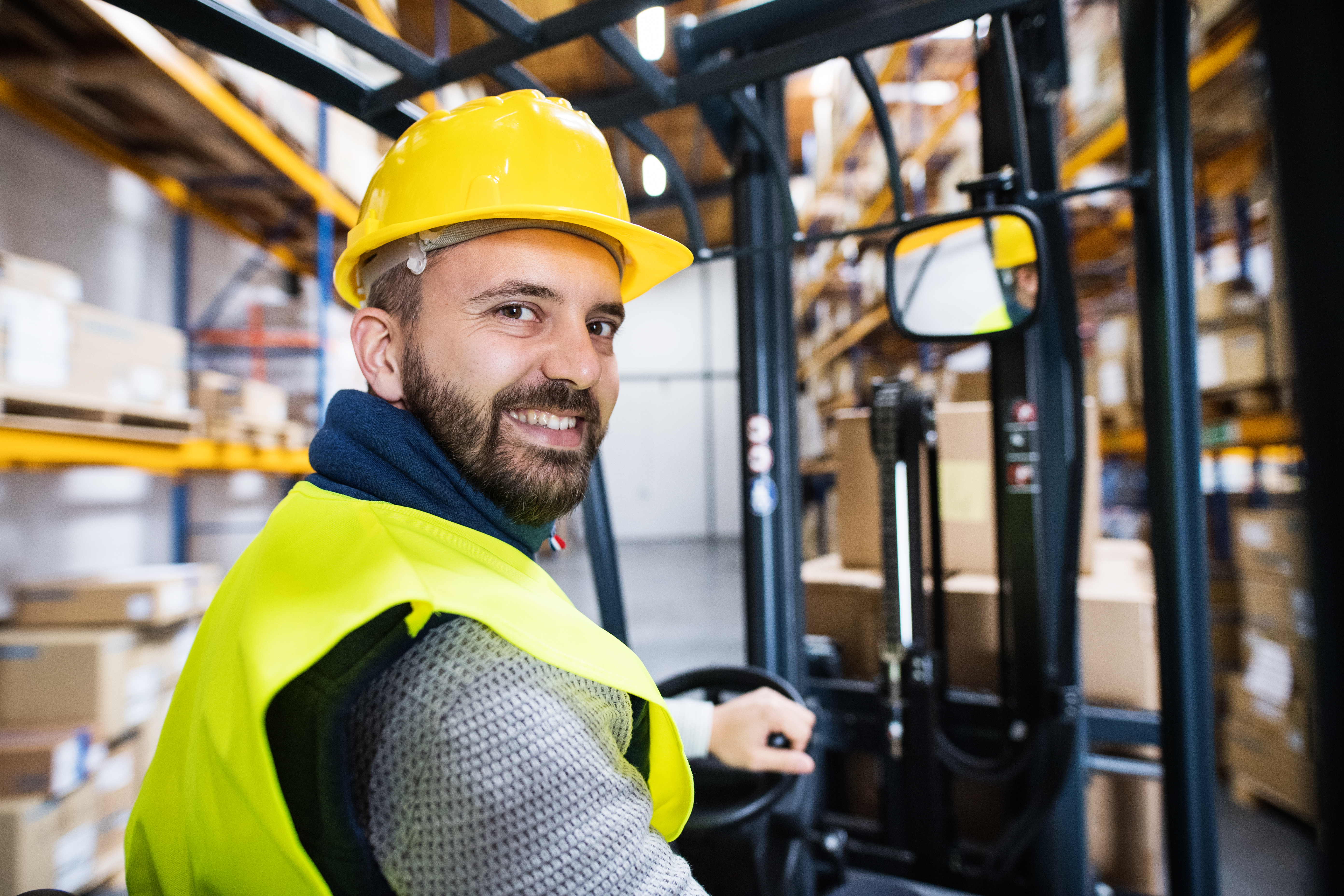 Warehouse worker happy at work on electric truck